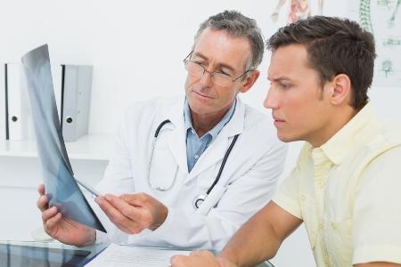 врач онколог показывает снимки пациенту