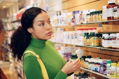 девушка выбирает витаминный комплекс