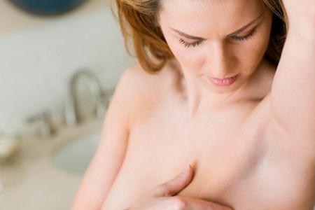 женщина проводит самообследование груди