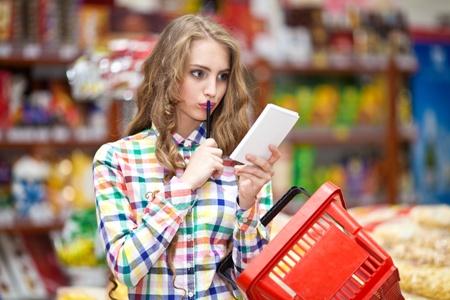 женщина задумалась в продуктовом магазине