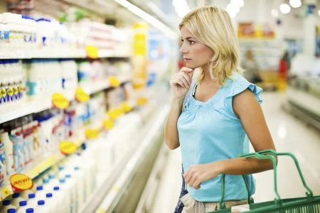 женщина в магазине выбирает кефир