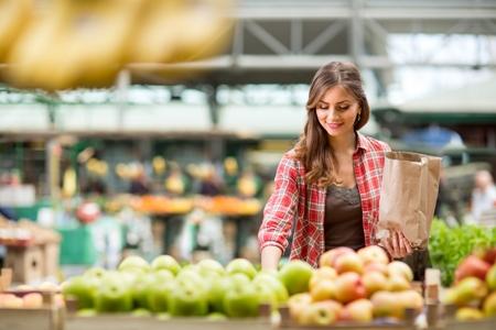 женщина в магазине выбирает фрукты