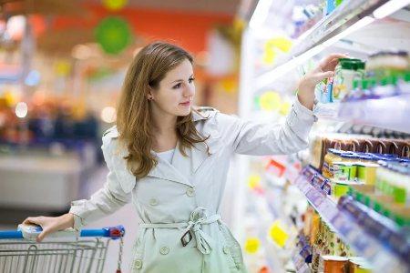 женщина выбирает молочные продукты в магазине