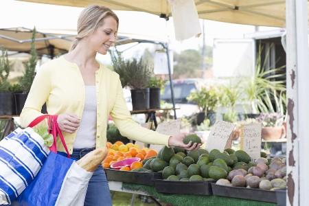 женщина выбирает плоды авокадо