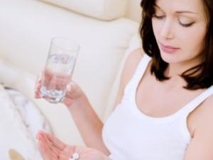 молодая мама пьет таблетки от стресса