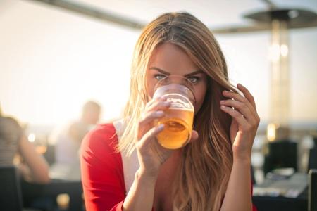 молодая мама пьет безалкогольное пиво