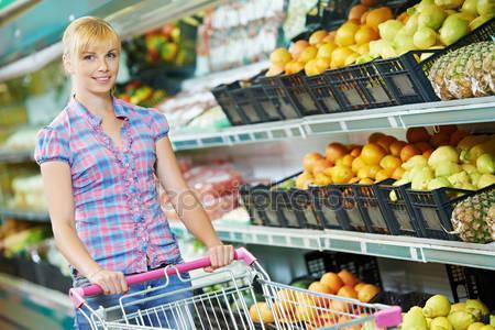 женщина в супермаркете покупает фрукты