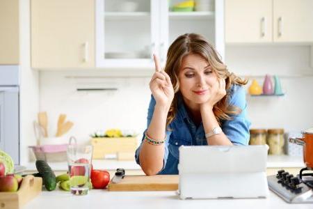 молодая мама ищет подходящий рецепт в интернете