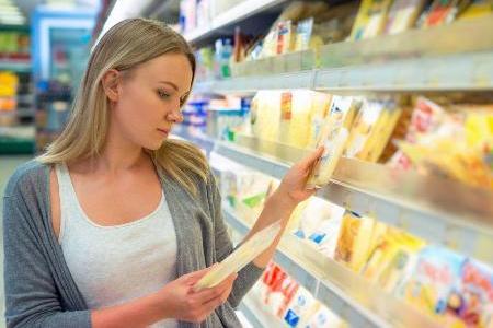 молодая мама выбирает сыр в супермаркете