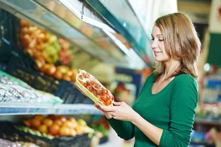 женщина в супермаркете выбирает помидоры